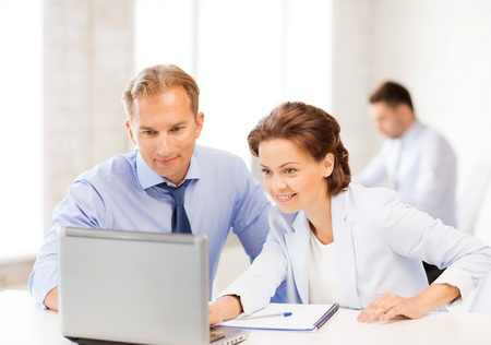 smiling businesswoman and businessman working with laptop in office photo
