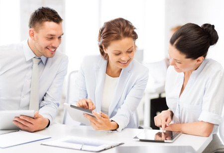 smiling business team working with tablet pcs in office photo