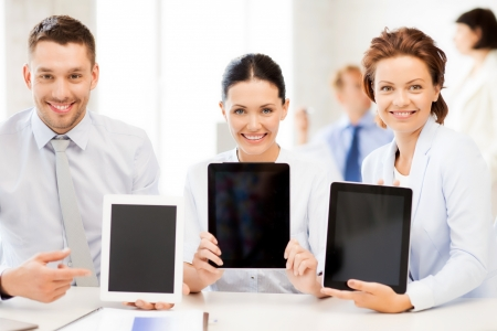 smiling business team showing tablet pcs in office Stock Photo - 20623531