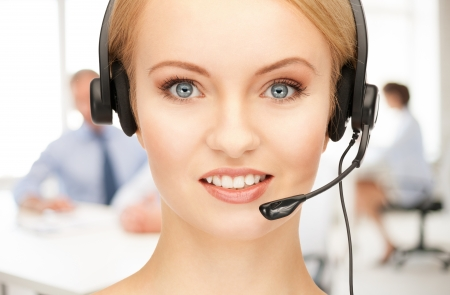 friendly female helpline operator with headphones in call centre photo