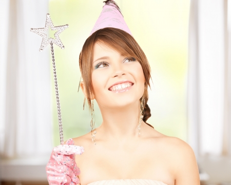 conjuring: happy girl in party cap with magic wand Stock Photo
