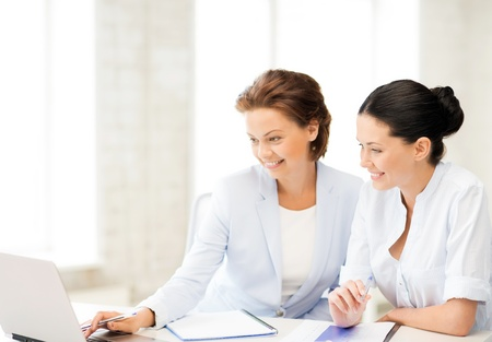 picture of two businesswomen working with laptop in office photo