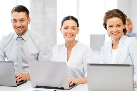 picture of group of people working with laptops in office photo