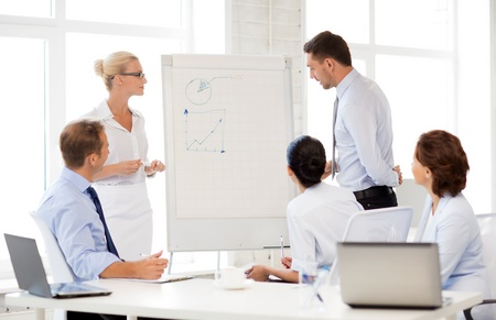 flipchart: smiling business team discussing something in office
