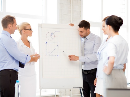 flip chart: smiling business team discussing something in office