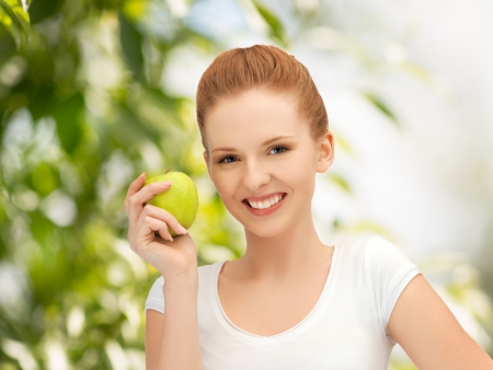 beautiful young woman with green apple at countryside photo