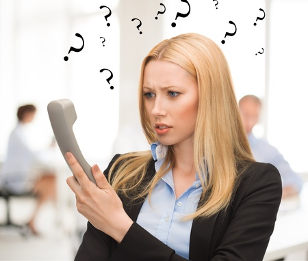 confused woman: bright picture of confused woman with phone in office Stock Photo