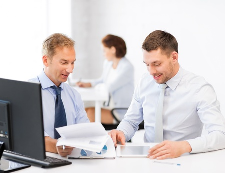 businessmen with notebook and tablet pc discussing graphs on meeting photo
