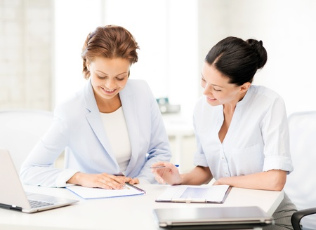 picture of two smiling businesswomen working in office photo