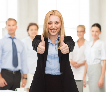 young businesswoman with thumbs up in office photo