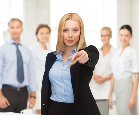 picture of attractive businesswoman pointing her finger at you photo