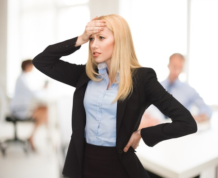business dilemma: stressed woman holding her head with hand in office