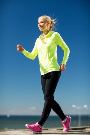 lifestyle outdoors: fitness and lifestyle concept - woman doing sports outdoors