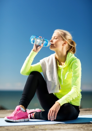 fitness and lifestyle concept - woman drinking water after doing sports outdoors photo