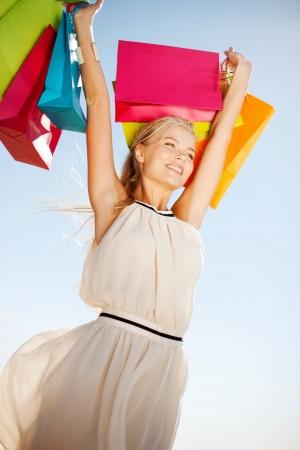chicas de compras: compras y concepto de turismo - mujer con bolsas de la compra Foto de archivo
