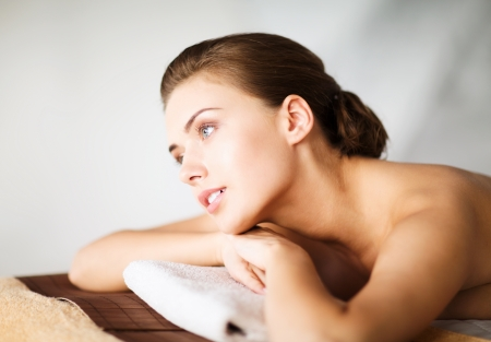 beauty and spa concept - woman in spa salon lying on the massage desk photo