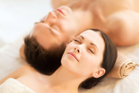 therapeutic massage: picture of couple in spa salon lying on the massage desks