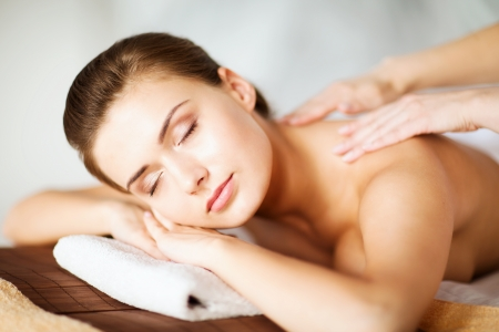 beauty and spa concept - woman in spa salon getting massage photo