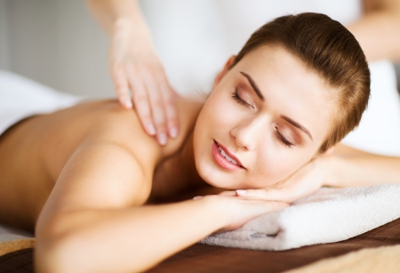 spa therapy: beauty and spa concept - woman in spa salon getting massage