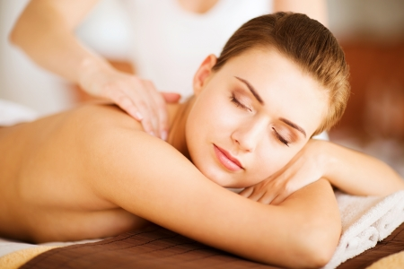 therapeutic: beauty and spa concept - woman in spa salon getting massage