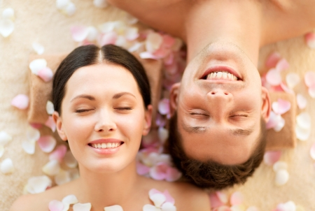 rejuvenation: faces of couple in spa salon lying on the massage desks Stock Photo