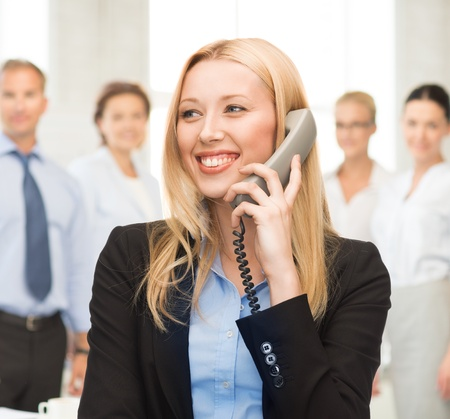 bright picture of smiling woman with phone in office photo