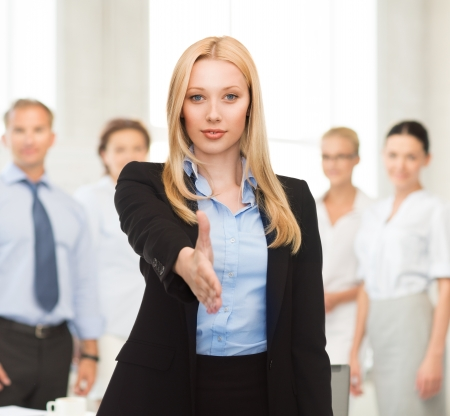 woman with an open hand ready for handshake in office photo