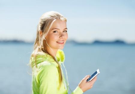 actief luisteren: fitness-en lifestyle-concept - vrouw doet sport en luisteren naar muziek in openlucht