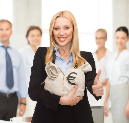 businesswoman with money bags showing thumbs up in office photo