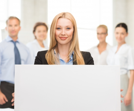 smiling businesswoman with white blank board in office photo