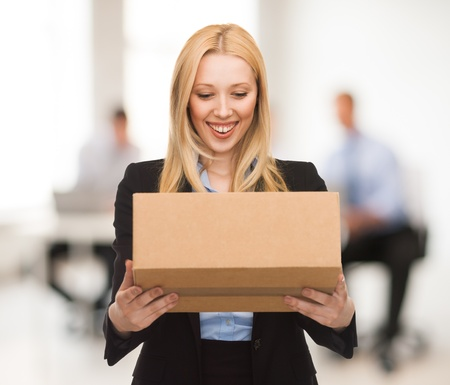 attractive businesswoman with cardboard box in office photo