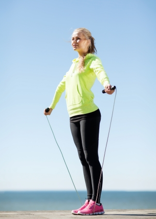 fitness and lifestyle concept - woman doing sports outdoors photo