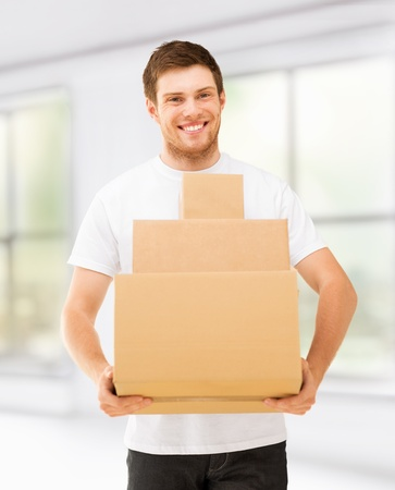 accomodation: picture of smiling man carrying carton boxes at home
