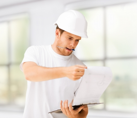 building contractor: male architect in helmet looking at blueprint at home