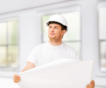male architect in helmet looking at blueprint at home photo