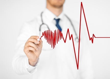 close up of doctor drawing electrocardiogram on virtual screen photo