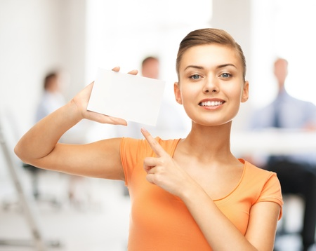 discounts: smiling woman pointing at white blank card in office Stock Photo