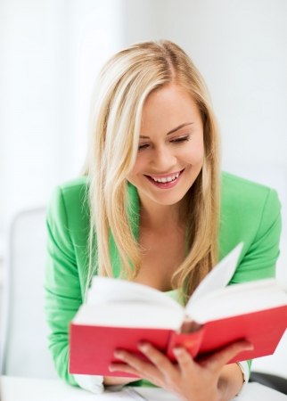 picture of smiling young woman reading book at school photo