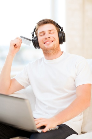 happy man with headphones and credit card listening to music at home photo