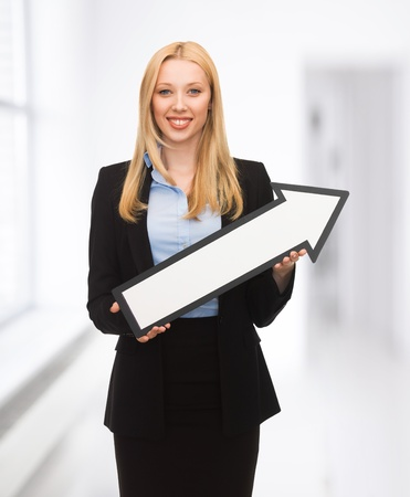 smiling businesswoman with direction arrow sign photo
