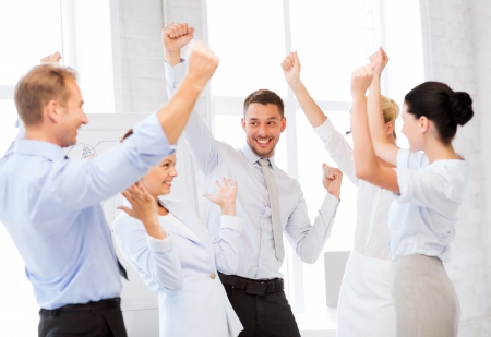 corporate woman: picture of happy business team celebrating victory in office