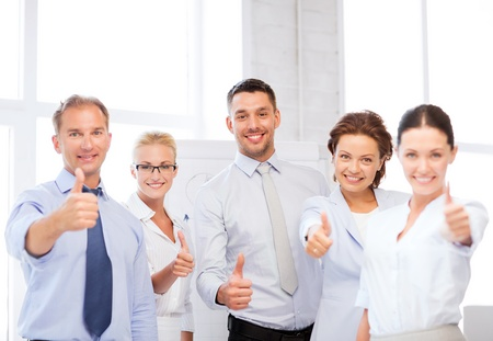 thumb up: picture of happy business team showing thumbs up in office Stock Photo