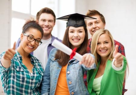 onderwijs - gelukkig meisje in afstuderen cap met certificaat en studenten