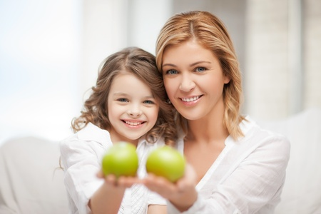bright picture of mother and daughter holding green apples Stock Photo - 20672244