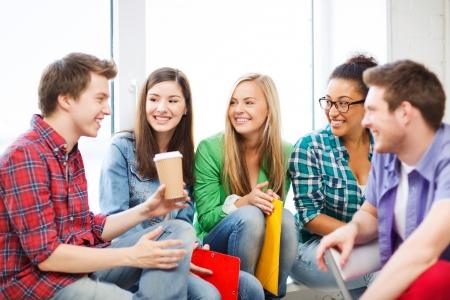 amigas conversando: concepto de la educación - los estudiantes se comunican y riendo en la escuela