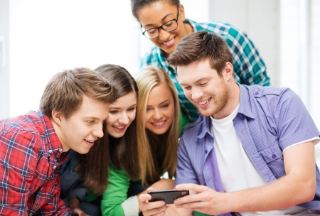 education and technology - group of students looking at smartphone at school photo