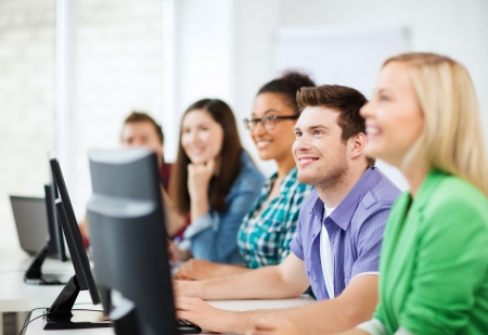 college: education concept - students with computers studying at school