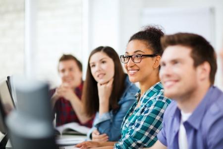 adolescentes estudiando: concepto de la educaci�n - los estudiantes con computadoras que estudian en la escuela