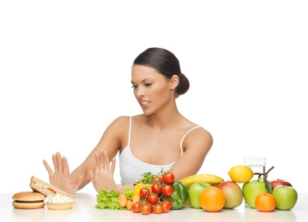 carbohydrates: picture of woman with fruits rejecting hamburger