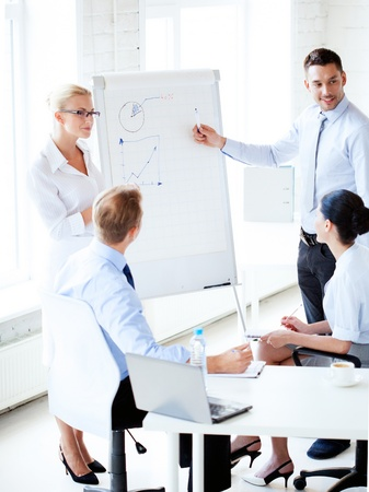 flip chart: young businessman pointing at graph on flip board in office Stock Photo